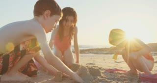 Three kids building sand castles on the beach during sunset