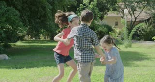 Three kids dancing in a circle on the lawn