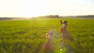 Three young kids running in a green field during sunset