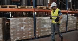 Tracking shot of a logistics worker walking in a warehouse