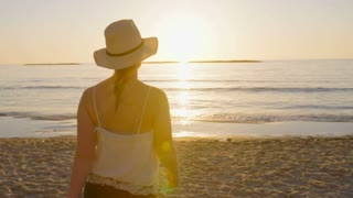 Tracking shot of a woman walking on the beach during sunset