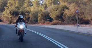 Travelling shot of a sports motorcycle driving on a curved mountain road