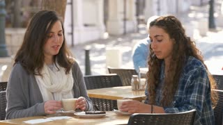 Two girls sitting in a cafe, drinking coffee