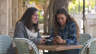 Two girls sitting in a cafe, texting on mobile phones