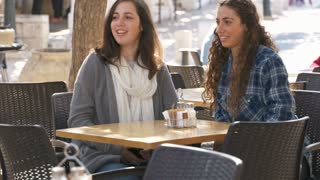 Two girls sitting in a cafe, waitress serving coffee