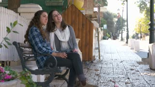 Two girls sitting on a bench on a promenade, talking