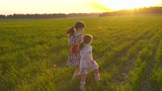 Two girls wearing dresses running in a green field during sunset