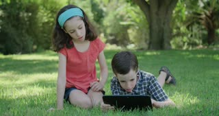 Two kids playing with tablet computer outdoors