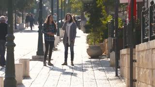 Two teenage girls walking down a promenade street, looking around at shops