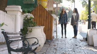 Two teenage girls walking down a promenade street, sitting on a bench, talking