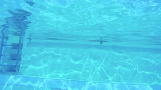 Underwater shot of two kids jumping and diving in a swimming pool