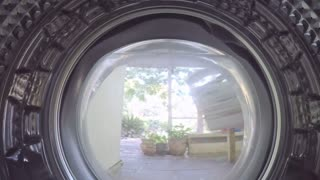 A GoPro view from inside a washing machine of a woman putting in dirty clothes