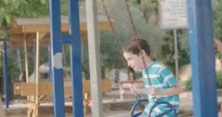 Boy and girl on swings in a playground - slow motion