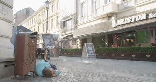 BUCHAREST, ROMANIA - AUGUST 5TH 2017: Homeless person laying in the busy street