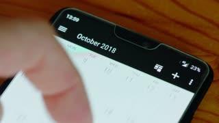 Close up of finger browsing through a smartphone calendar
