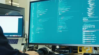 computer programmer sitting in front of a screen coding software