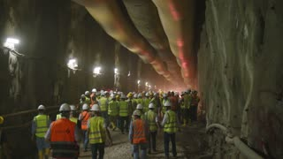 Construction workers walking into a large tunnel