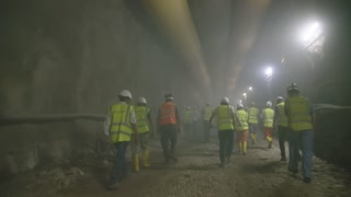 Construction workers walking out from a dark smoke filled tunnel