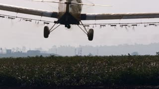 Crop duster spraying chemicals over a cotton field - slow motion