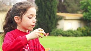 cute little girl blowing soap bubbles in slow motion