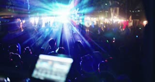 DJ playing music in a large outdoor dance party with people dancing