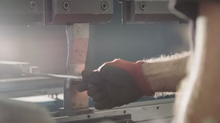 Factory worker bending metal parts with a machine