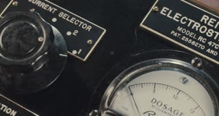 Hand operating vintage electrical switchboard with dials and switches