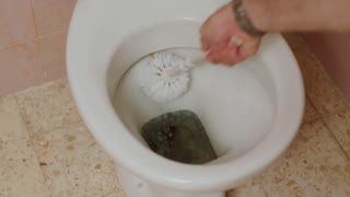 Hand with brush cleaning a dirty toilet