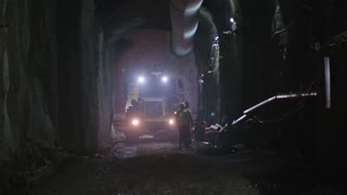 Large construction trucks working inside a tunnel