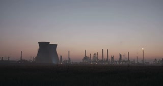 large oil refinery silhouette against the sunsrise with chimneys and smoke stacks