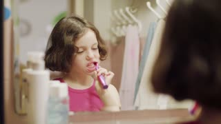 Little girl brushing her teeth in front of the mirror