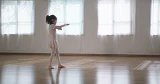 Little girl dancing alone in a studio