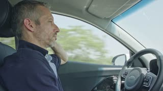 Male driver sitting in an autonomous car, letting the car drive by itself