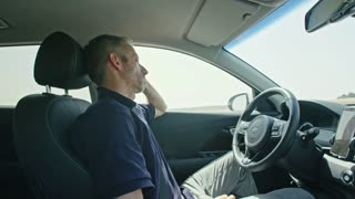 Male driver sleeping while the autonomous car drives by itself