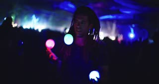Man juggling with light balls during a night party