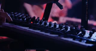 Musician playing the keyboard and sampling pad during a rock concert