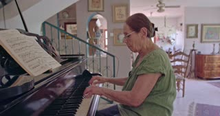 Old woman playing a grand piano at her home