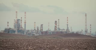 Save our planet - children with gas masks near a big oil refinery
