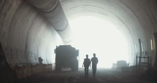 silhouette of construction workers walking on a large tunnel construction site