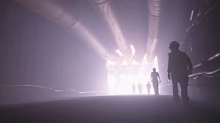silhouette of many construction workers walking out from a large tunnel