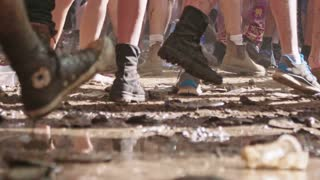 Slow motion footage - feet of people dancing in a nature trance party