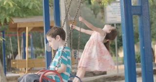 Slow motion footage of young children swinging on swings in a playground afternoon in the sun