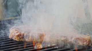 Slow motion of a large beef sirloin steak grilled on a charcoal grill
