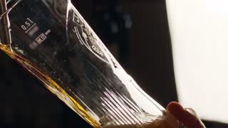 Slow motion of cold beer poured into a tall glass