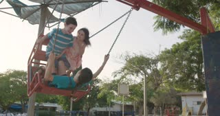 Slow motion of kids on a red swing in the park