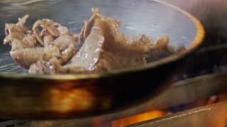 Slow motion of roast beef cooked in a frying pan with flames
