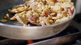 Slow motion of shawarma cooking in a frying pan