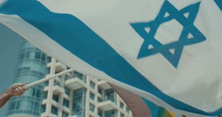 Slow motion shot of the rainbow flag with the Israeli flag waving high at a pride parade