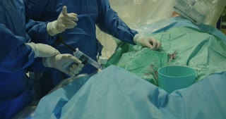 Surgeons inserting a catheter during a Cardiac catheterization procedure