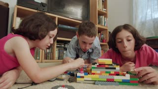 Three kids playing with lego bricks at home